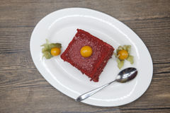 Red Velvet, fresh delicious diet cake with berry Physalis at Dukan Diet on a porcelain plate with a spoon on a wooden background Stock Photo