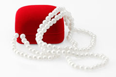 Red velvet gift box and pearl necklace Stock Photos