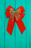 Red velvet and gold Christmas bows hanging on antique teal blue weathered wood door Royalty Free Stock Photos