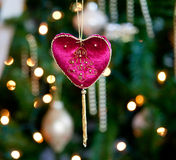 Red velvet heart in front of xmas tree. Close up of red velvet heart ornament in front of out of focus christmas decorations royalty free stock image