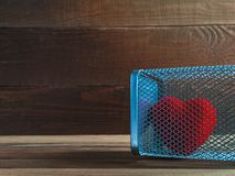 Red Velvet Heart in a Mesh Cage on a Rustic Wooden Background. Love, Home Violence, Loneliness, Freedom and Heartache Concept.  stock images