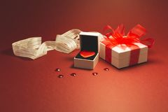 I give you my heart. A red velvet heart in a white jewelry box, a white gift box with red ribbon and small shiny red decorative hearts on red background Royalty Free Stock Photography