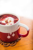 Red Velvet Hot Chocolate. A cup filled with red velvet hot chocolate topped with cream cheese and dusted with cinnamon Royalty Free Stock Image
