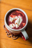 Red Velvet Hot Chocolate. A cup filled with red velvet hot chocolate topped with cream cheese and dusted with cinnamon Royalty Free Stock Images