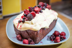 Red velvet Loaf. A red velvet loaf cake with cream cheese topping and strawberries, raspberries and red currents Stock Photo
