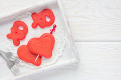 Red velvet pancakes with xo sign & x28;hugs and kisses& x29; and heart on a wooden tray, horizontal, top view, copy space Royalty Free Stock Photos