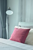 Red velvet pillow setting on bed with standing lamp next to bed Royalty Free Stock Photo