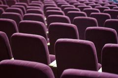 Red velvet seats for spectators royalty free stock photography