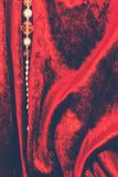 Red velvet and a string of beads Royalty Free Stock Photos