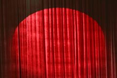 Red velvet theater curtain. With spotlight Stock Images