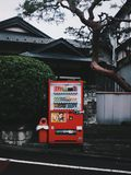 Red Vending Machine In Front Of A House Royalty Free Stock Photography