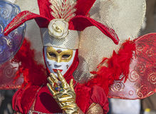 Red Venetian Disguise. Venice, Italy- February 18th, 2012: Environmental portrait of a person wearing a beauty red Venetian costume during a the Venice Carnival stock image