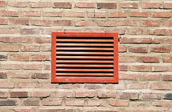 Red ventilation grill. On a wall made of bricks Stock Photo