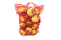 Red vertical standing string bag of apples Royalty Free Stock Images