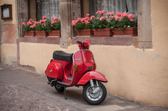 Red vespa scooter near traditional house in Colmar Stock Image