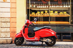 Red Vespa scooter parked in front of the bakery in Rome, Italy Royalty Free Stock Image
