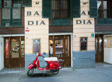 Red vespa scooter parked in front of Bar Dia Stock Image
