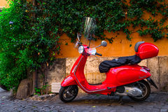 Red Vespa scooter parked on old street in Rome, Italy stock photography