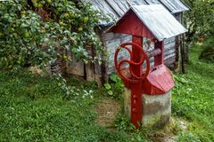 The red village well near a wooden country house stock photo