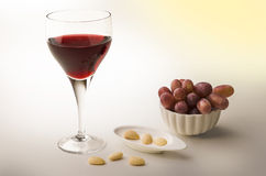 Red vine in a glass with almonds and grapes Stock Photography