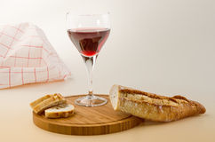 Red vine in a glass with bread on a wooden plate Stock Image