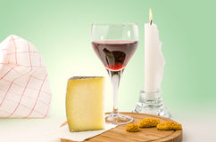 Red vine in a glass with cheese and candle Stock Photography