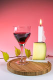 Red vine in a glass with cheese and candle 1 Stock Photos