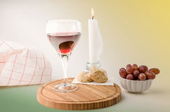 Red vine in a glass with grapes and candle Royalty Free Stock Photography