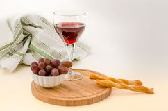 Red vine in a glass with grapes and grissini 1 Royalty Free Stock Image