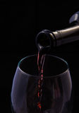 Red vine pouring from bottle. Into a glass Royalty Free Stock Photo