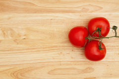 Red vine ripe tomatoes on wood background Royalty Free Stock Photo