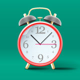 Red vintage alarm clock on green background Stock Photo
