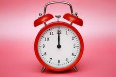 Red vintage alarm clock on pink pastel background. Stock Photo
