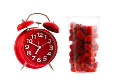 Red vintage alarm clock and raspberry, healthy breakfast concept Royalty Free Stock Photo