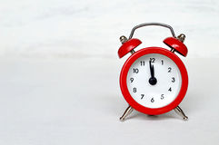 Red vintage alarm clock striking midnight (or midday) Stock Photography