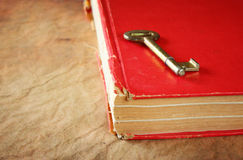 Red vintage book with golden classic key on cover Royalty Free Stock Photos
