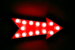 Red arrow: red vintage bright and colorful illuminated display arrow sign. Red vintage bright and colorful illuminated display arrow sign with light bulbs Royalty Free Stock Images