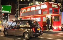 Red vintage bus and classic style taxi in London. Royalty Free Stock Images