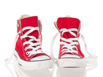 Red vintage canvas sneakers untied. On white background Royalty Free Stock Photos