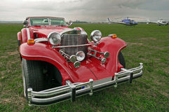 Red vintage car - Excalibur. Helicopters in the background. View of the front of a red vintage car Excalibur Stock Image