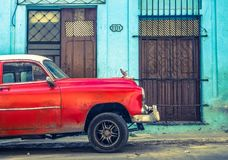 Red vintage car in Havana. An old Packard in front of a blue house in Havana Stock Photos