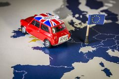 Red vintage car with Union Jack flag and brexit or bye words over an UE map and flag. Royalty Free Stock Photo