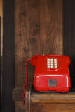 Red vintage coin Telephone. Old red telephone on the wooden cabinet Royalty Free Stock Photos