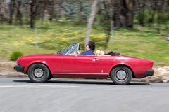 Red vintage convertible car driving on country road Royalty Free Stock Photography