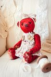 Red vintage handmade plush art cute teddy bear toy. Indoors multicolored vertical image with retro filter Royalty Free Stock Image