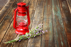 Red vintage kerosene lamp, and lavender flowers on wooden table. fine art concept. Stock Images