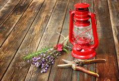 Red vintage kerosene lamp, and sage flowers on wooden table. fine art concept. Stock Photo