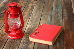 Red vintage lamp and red antique book on wooden table. vintage still life design. Stock Photos