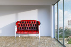 Red vintage leather sofa in modern room with parquet and urban c Stock Images