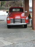 Red vintage pick up under carport for local grocery business. Red, lots chrome, grill, headlights, ad for market Stock Photos